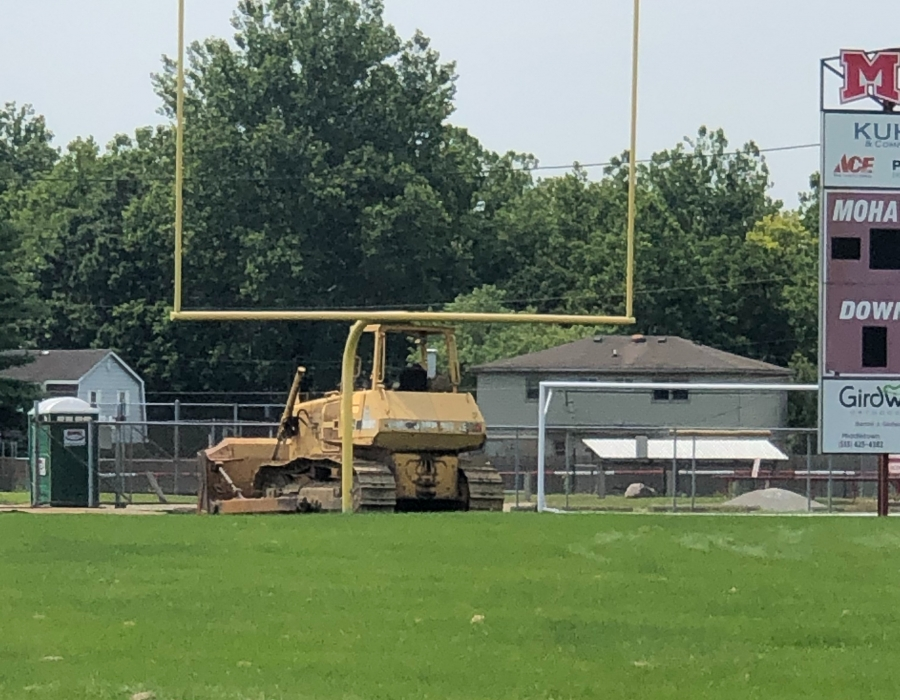 An excavator is present on July 22, 2021 to begin breaking ground for the new turf field.